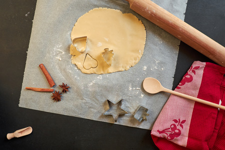 Top view of cookie dough, cookie cutter, rolling pin, and utensils