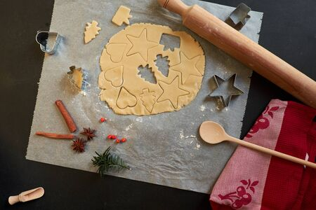Top view of cookie dough, cookie cutters, rolling pin, cinnamon, towel