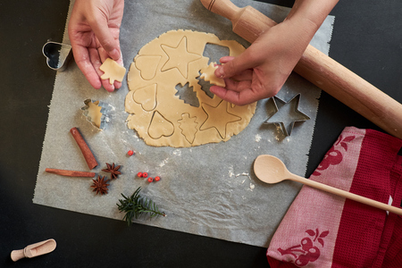 Top view of two hands cutting cookies with dough, cutters and rolling pin