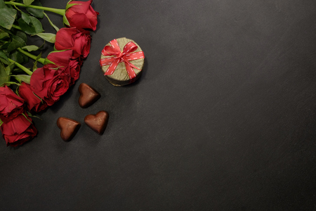 Red roses, gift box and chocolate hearts with copy space