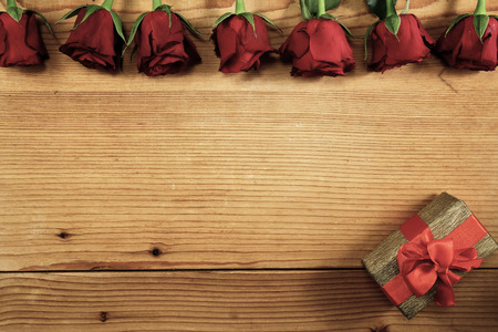 Red roses and gift box on wood with copy space
