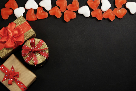 Three gift boxes with red candies with copy space on black Stock fotó