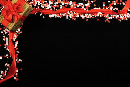 Red and white confetti with gift box on black