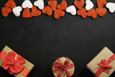 Red candies and gift boxes with copy space on black