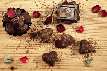 Assorted chocolate with rose petals on the wood