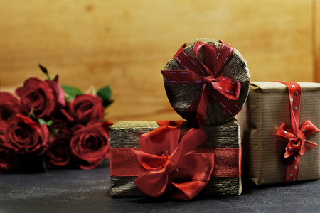 Three romantic gift boxes and red roses