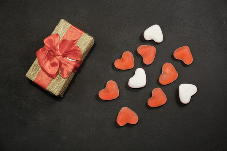 Gift box and heart shaped candy on black