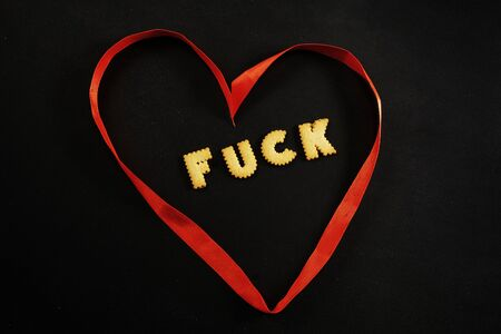 Heart made of red ribbon with word fuck inside Stock fotó