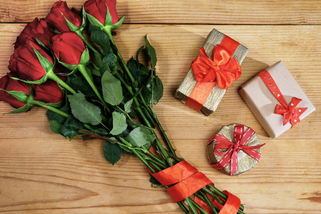 Bunch of red roses with ribbon and three gift boxes