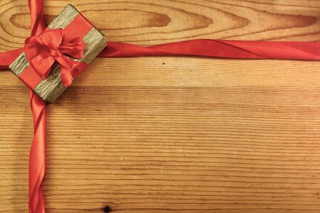 Gift box and ribbons with copy space on wood