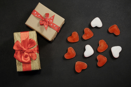 Two gift boxes and heart shaped candy on black