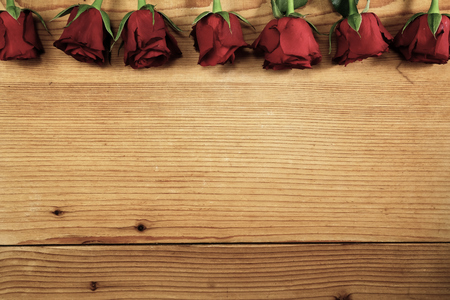 Red roses on the textured wood with copy space Stock fotó
