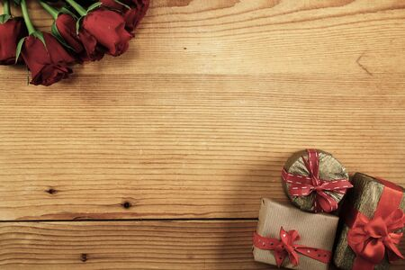 Red roses and three gift boxes on wood with copy space Stock fotó