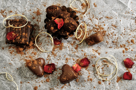 Many Chocolate hearts and truffles on white paper