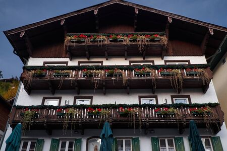 Looking up at chalet balconies with flowers in Alps