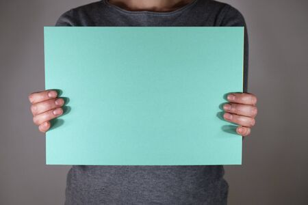 Two hands holding blue paper sheet Stock fotó