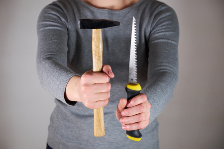 Woman holding saw and hammer
