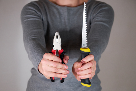 Woman holding tools in both hands