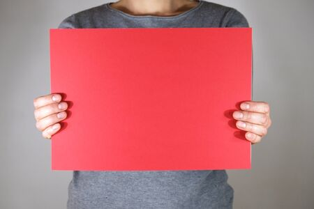 Two hands holding blank red paper sheet Stock fotó