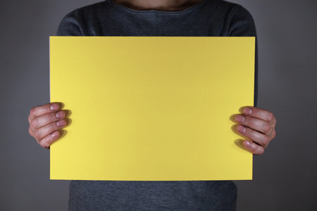 Two hands holding yellow paper sheet