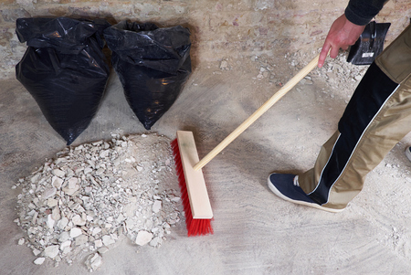 Workman sweeping the rubble with broom Stock fotó - 81580169