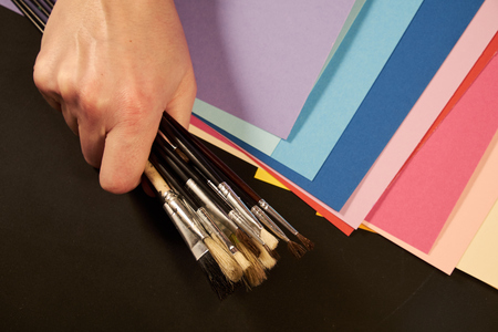 Hand holding many painting brushes with multicolour paper sheets
