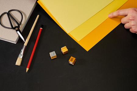 Hand choosing yellow shade with creativity tools on blackboard