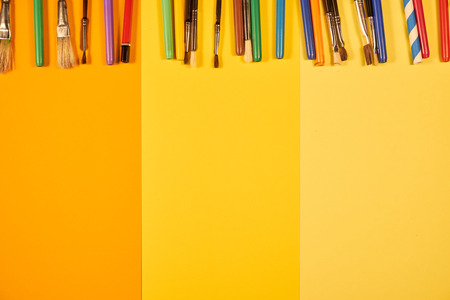 Brushes and multicoloured pens on yellow copy space