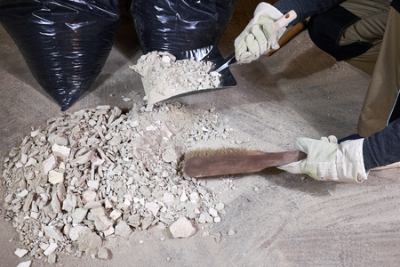 Worker cleaning rubble with brush and dustpan Stock fotó