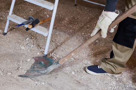 Cleaning construstion rubble with spade Stock fotó