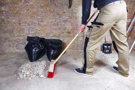 Worker sweeping rubble and dust with broom