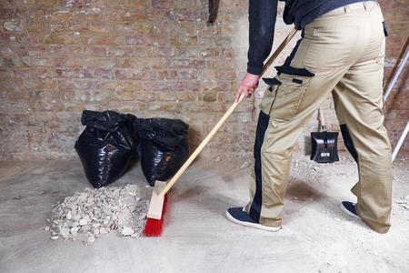 Werknemer vegen puin en stof met bezem
