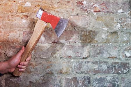 Hand holding axe against brick wall Stock fotó