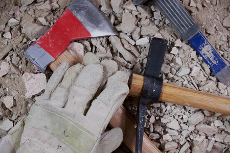 Axe, gloves and construction tools on pile of rubble