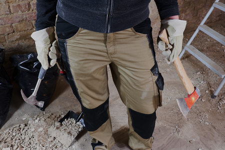 Work person holding tools with construstion in the background