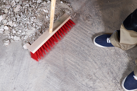 Workman sweeping the rubble on the floor with a broom Stock fotó