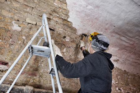 Worker on ladder removing plaster from brick wall