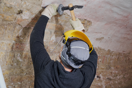 Worker removing plaster from the wall with tools Stock fotó - 81603122