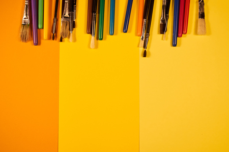 Copy space with brushes and multicoloured pens on yellow shades