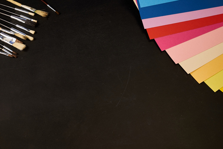 Multicolour sheets of paper and brushes with copy space on black Stock fotó - 81898203