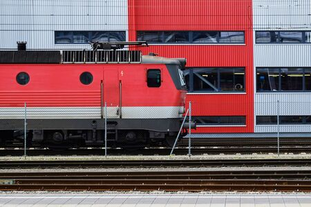 Red electric locomotive on the train station