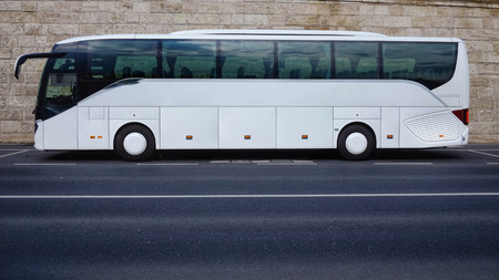 White tourist bus parked on empty road