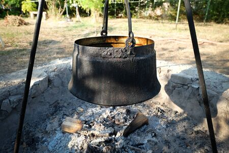 Big cooking pot in the fire pit with ashes Stock fotó - 129074589