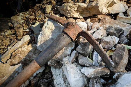 Old rusty hack axe on the heap of rocks in the garden Stock fotó - 129074603