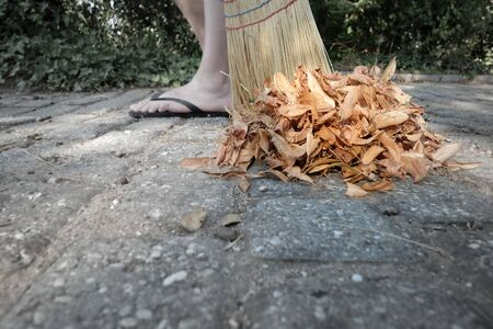 Person sweeping dry leaves with a broom in the garden Stock fotó