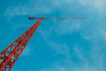 View of the red construction crane in the blue sky