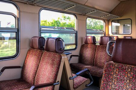Interior of old european train with chairs in red colors