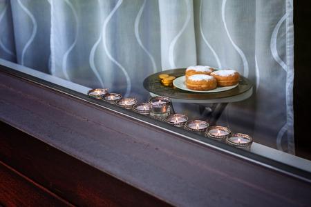 gelt: The Symbols of Hanukkah - nine-branched mehorah Hanukiah , sufganiyot and chocolate coins in the window Stock Photo
