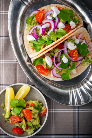 tortilla de maiz: Chicken Tacos with vegetables served on the table.
