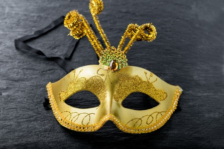 A gold Carnival mask on a black background.